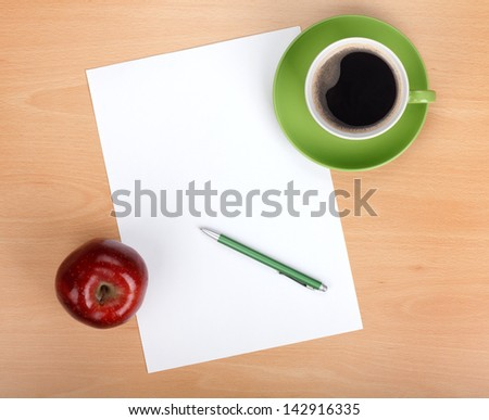 Blank paper with pen, coffee cup and red apple on wood table - stock photo