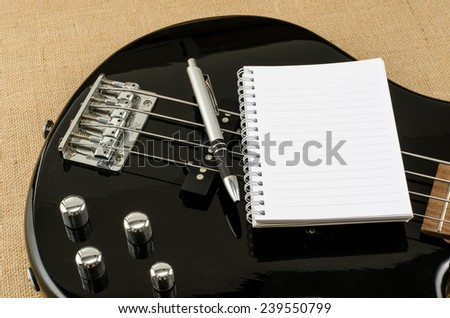 Blank paper with pen on electric bass guitar on brown sack background - stock photo