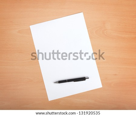 Blank paper with pen on wood table - stock photo