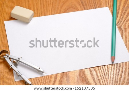 Blank paper with pencil, compass and eraser on wooden background - stock photo