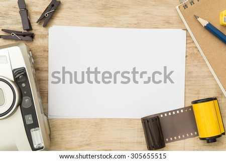 Blank paper with photo film in cartridge and film camera on wooden table. - stock photo