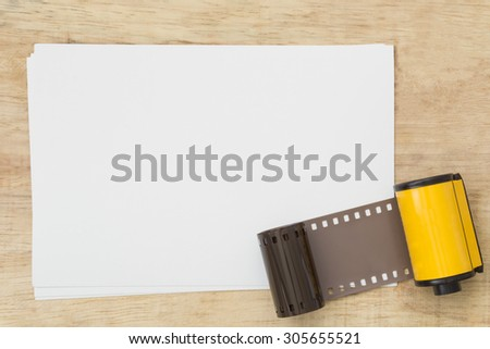 Blank paper with photo film in cartridge  on wooden table. - stock photo