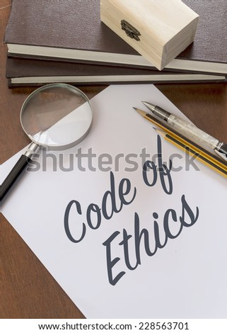 Blank paper with phrase Code of Ethics on desk. - stock photo