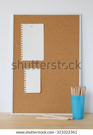 Blank papers on cork board and pencils on wood table over white cement wall background, template - stock photo