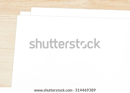 Blank papers on wooden table background, top view