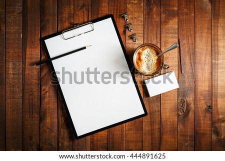 Blank paperwork template for designers. Responsive design mockup on vintage wooden background. Blank paper, letterhead, coffee cup, business cards and pencil on wooden table background. Top view. - stock photo