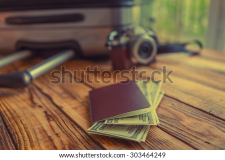 Blank passport and camera with US dollars on wood table ( Filtered image processed vintage effect. )