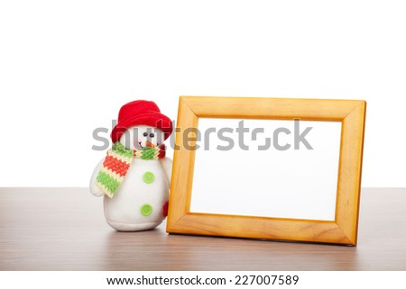 Blank photo frame and christmas snowman on wooden table. Isolated on white background - stock photo