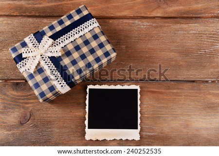 Blank photo frame and present box on wooden table background - stock photo