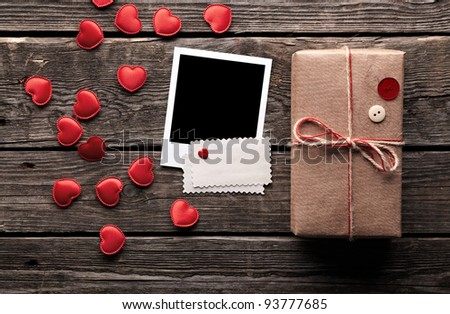 Blank photo frame and vintage gift box (package) with blank gift tag on old wooden background. - stock photo