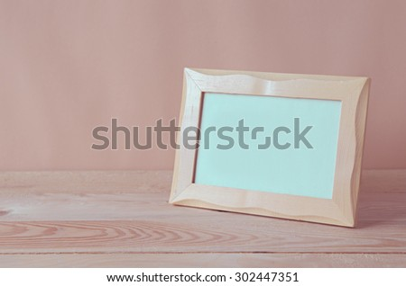 blank photo frame on wooden table - stock photo