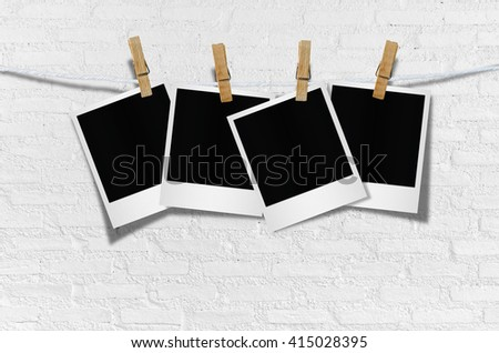 Blank photo frame with clothespin hanging on wooden background.