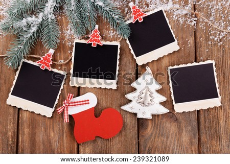 Blank photo frames and Christmas decor with snow fir tree on wooden table background - stock photo