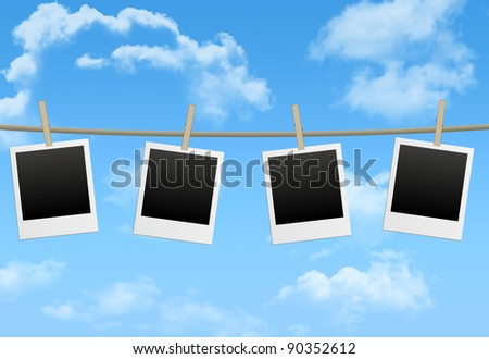 blank photo frames hang by wooden peg on blue sky - stock photo