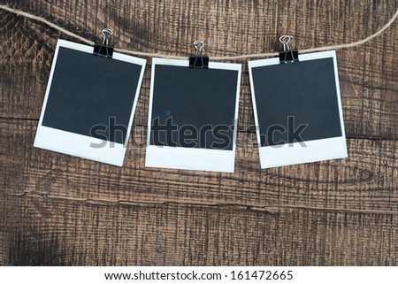 Blank photo frames on a wooden background. Black old pictures. - stock photo