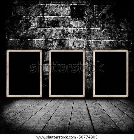 Blank photo frames on grunge wall texture - stock photo