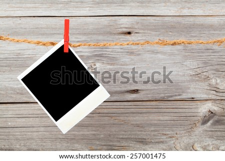 Blank photo hanging on a clothesline over wooden background - stock photo