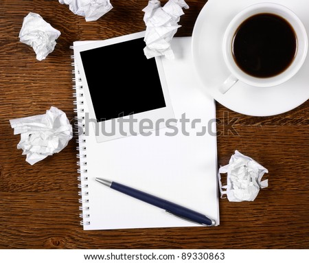 Blank photo on notepad with pen on wooden desk - stock photo