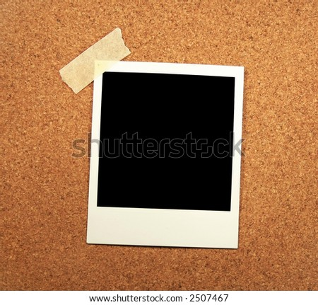 Blank photo with one corner taped to a corkboard. - stock photo