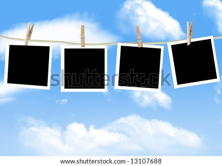 Blank photographs hanging on a clothesline against a blue sky - stock photo