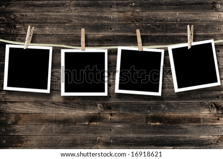 Blank photographs hanging on a clothesline against a wood background - stock photo