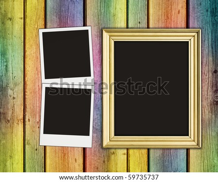 blank photos and frame on vintage multicolored wooden background