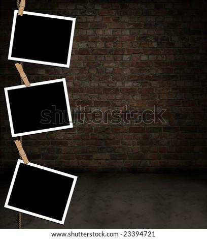 Blank photos hanging grungy brick room - stock photo