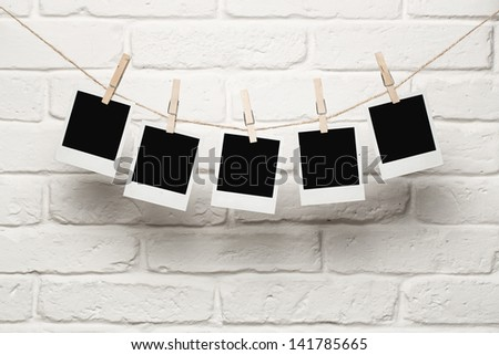 Blank photos hanging on a clothesline over brick wall background with copy space - stock photo