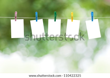 Blank photos hanging on a clothesline, summer defocus background - stock photo