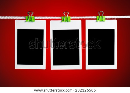 blank photos hanging on rope, blue background - stock photo