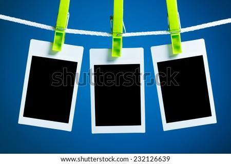 blank photos hanging on rope, blue background - stock photo