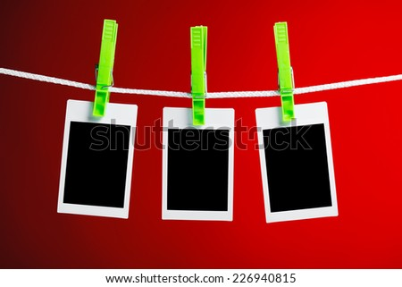 blank photos hanging on rope, red background - stock photo