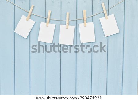 Blank photos hanging on rope with clothespins on blue wooden background - stock photo