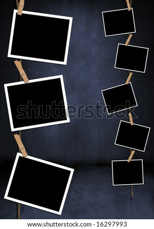 Blank photos hanging vertically in a blue grungy room - stock photo