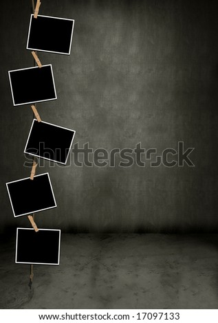 Blank photos hanging vertically in a dark grungy room - stock photo