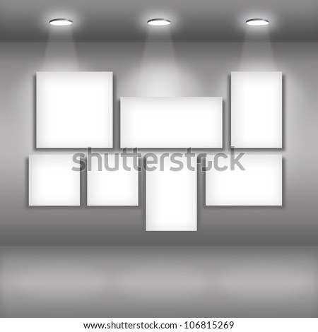 Blank picture frames on wall in dark gallery interior - stock photo