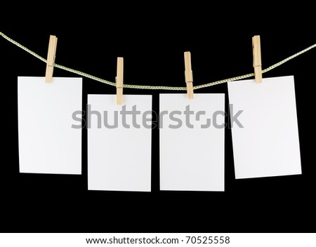 Blank pieces of paper and wooden clothespins isolated on black - stock photo