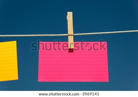 blank Pink index card on a clothesline with blue sky background - stock photo