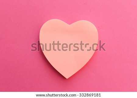 Blank pink paper note heart shape on pink background with copy space - stock photo