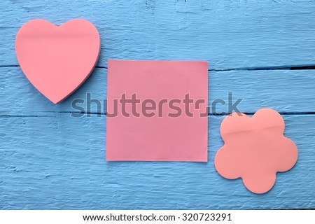 Blank pink paper note in three different shapes - flower, square and heart shape on grunge blue wooden background with copy space - stock photo