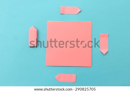 Blank pink stick note paper on blue background and arrows shape stick notes around it - stock photo