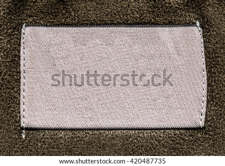 blank pinkish-gray textile label on brown textile background