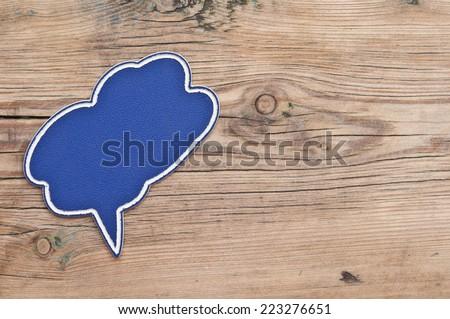 Blank plastic speech bubble on wood background  - stock photo