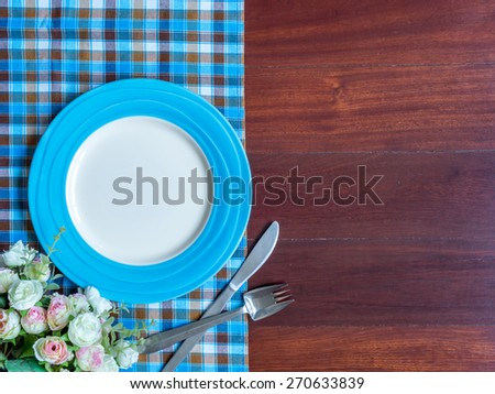 Blank plate with checked tablecloth and flower on wooden table background - stock photo
