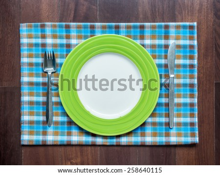 Blank plate with fork and knife on checked tablecloth over wooden table background - stock photo