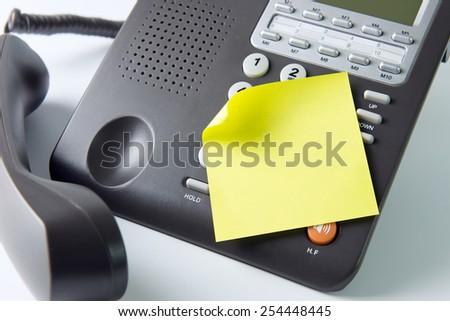 Blank post it note pad on landline telephone - stock photo