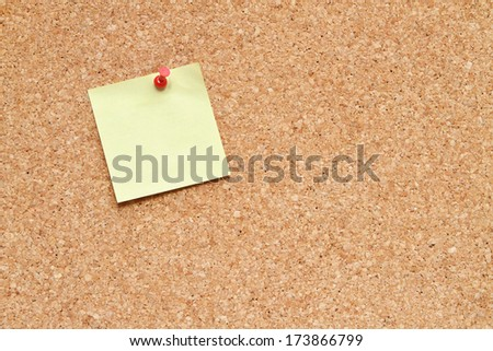 blank post it note pinned to a cork board / bulletin board  - stock photo
