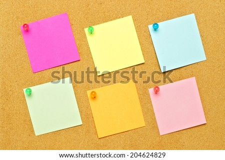 Blank post it notes of various colors with tacks on a bulletin board