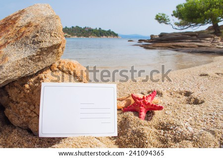 Blank postcard and red starfish on the sandy beach  - stock photo