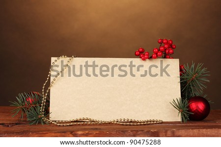blank postcard, Christmas balls and fir-tree on wooden table on brown background